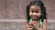 Happy little Asian girl smiling at camera and playing Stock Footage
