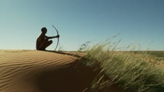 Kalahari bushman sitting on top of dune wide - stock footage
