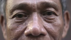 Eyes and face of serious old asian man looking at camera - stock footage