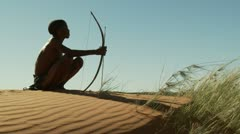 Kalahari bushman sitting on top of dune medium Stock Footage