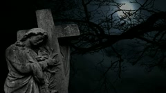 Graveyard statue set against timelapse bare tree and full moon Stock Footage