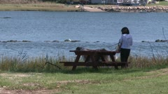 Woman walks dog by the water - stock footage