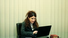 Jubilating female clerk with laptop sitting in office Stock Footage