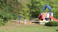 Children swinging on swings at a small playground (2 of 5) Stock Footage