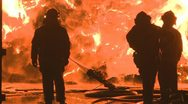 Firemen silhoueted at a large blaze Stock Footage