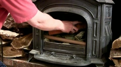 Building fire in wood stove; add kindling Stock Footage