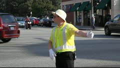Man in yellow vest controlling traffic Stock Footage