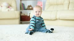 Baby boy sitting on the carpet in the room Stock Footage