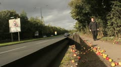 Man and traffic pass an apple tree Stock Footage
