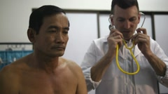 Doctor working and visiting old sick man in clinic Stock Footage