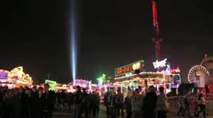 Fairground - wide shot of crowds with huge rides behind them Stock Footage