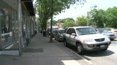 Cars parked along road in front of stores Stock Footage