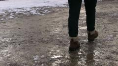 Female in boots walking on winter path Stock Footage