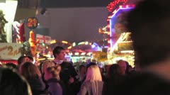 Fairground - wide shot of crowds with ride behind them Stock Footage