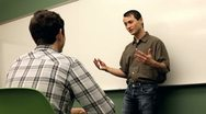 Teacher talking to student in classroom Stock Footage