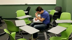 Man surrounded by chairs in classroom Stock Footage