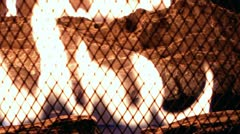 Flame behind fireplace mesh close up Stock Footage