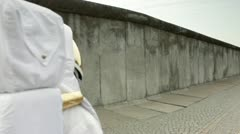 WS, Lockdown astronaut walking up to a surrounding wall in a city, knocking and - stock footage