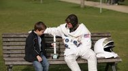 Stock Video Footage of MS, Lockdown of an astronaut and a young boy sitting on a park bench playing