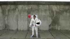 WS, Lockdown, front view of an astronaut on a city sidewalk holding and then Stock Footage