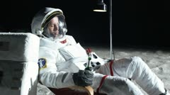 SLO MO, MS, Lockdown, astronaut on the moon sitting in a reclining chair, - stock footage