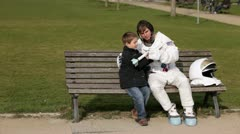WS, Lockdown of an astronaut and a young boy sitting on a park bench playing Stock Footage