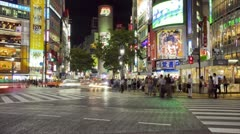 Pedestrians at Shibuya Crossing at night in Downtown Tokyo, Japan - Time Lapse Stock Footage