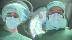 Close-up low angled handheld shot of doctor and a nurse in a surgical mask and - stock footage