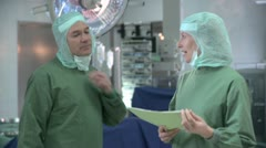 Medium shot lockdown of two doctors wearing surgical scrubs standing in an - stock footage