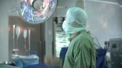 Medium shot lockdown of a doctor wearing surgical scrubs standing in an Stock Footage