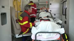 Medium lockdown shot of two paramedics attending to a patient lying on a Stock Footage