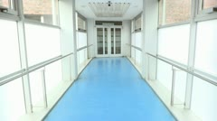 Full dolly shot of a hospital corridor where a doctor and nurse are walking and Stock Footage