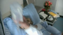 Extreme close-up lockdown shot of a doctor hanging up an IV drip while a patient Stock Footage