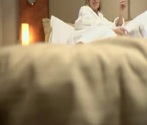 Full tilt up shot of a woman in a bathrobe lying on a bed in a hotel room and Stock Footage