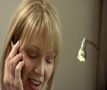 Close-up lockdown shot focus on foreground of a woman talking on a cell phone Stock Footage
