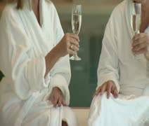 Medium lockdown shot midsection of a man and a women wearing bathrobes while - stock footage