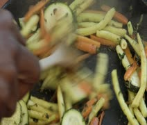 Extreme close-up lockdown shot of a human hand stirring sauteed vegetables in a Stock Footage