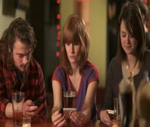 MS, PAN, Selective Focus, Three friends sitting at a bar using their mobile Stock Footage