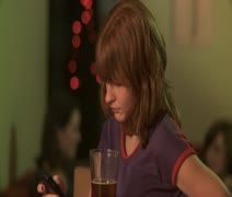 MS, Selective Focus, A woman at a bar using a mobile phone when a man approaches Stock Footage