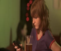 CU, Selective Focus, A woman sitting at a bar using a mobile phone when a man Stock Footage