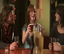 CU, PAN, Four friends sitting at a bar drinking beers when one woman proposes a - stock footage