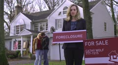 MS, Real estate agent holding FORECLOSURE sign, couple in background Stock Footage