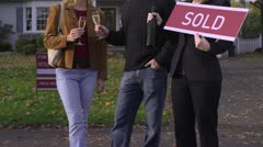 MS, TU, Couple holding champagne glasses, real estate agent holding SOLD sign Stock Footage