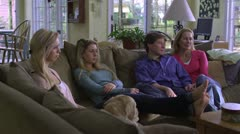 MS, DS, family of four sitting on a couch in their living room, watching TV Stock Footage