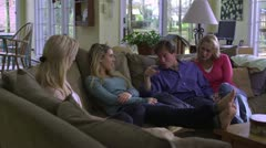 MS, DS, family sitting on a couch in living room listening to Dad tell a funny Stock Footage