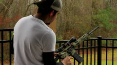 White male shooting machine gun  AR 15 multiple shot Stock Footage