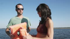 MS, Lockdown of a couple on a boat helping each other put on life jackets Stock Footage