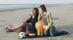 SLO MO, WS, Lockdown of a young couple having a picnic at the beach Stock Footage