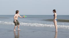 SLO MO, WS, TS of a young couple playing with squirt guns at the beach Stock Footage