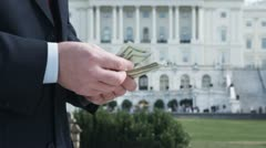 CU, Lockdown of man counting money in front of the US Capitol Building, - stock footage